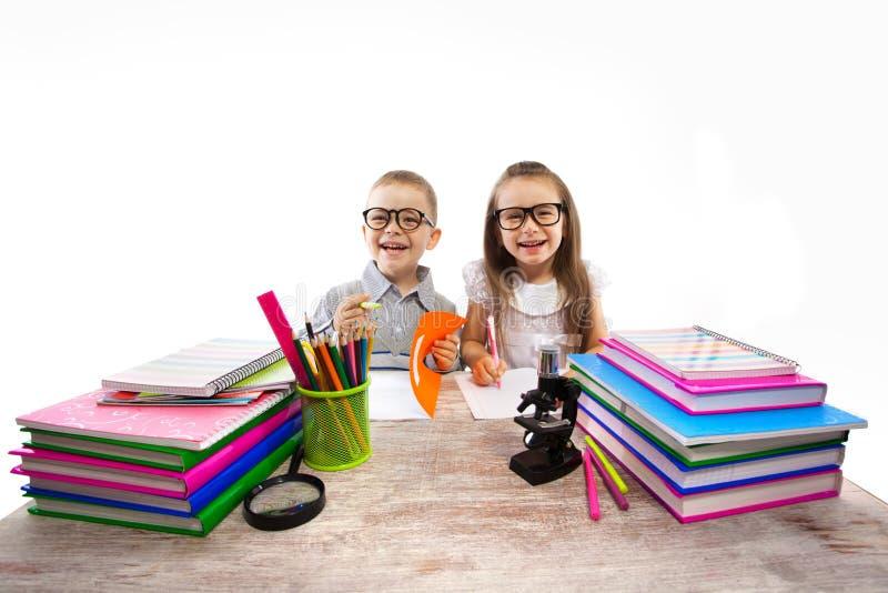 Zwei Kinder an den Tabellenkindern, die Hausarbeit tun stockbilder