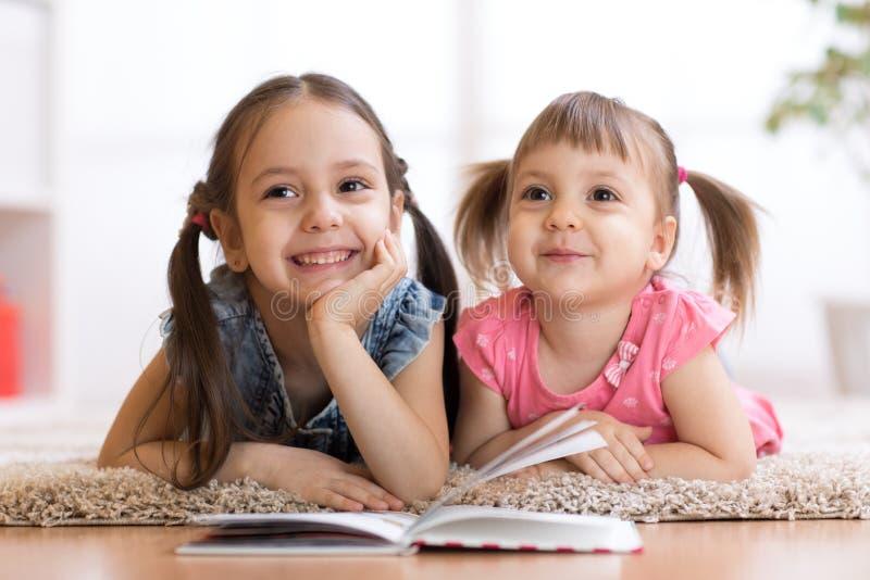 Zwei Kinder, die auf Boden- und Lesebuch liegen lizenzfreie stockbilder