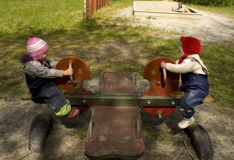 Zwei Kinder, die auf einem Schaukel Totter spielen lizenzfreies stockfoto