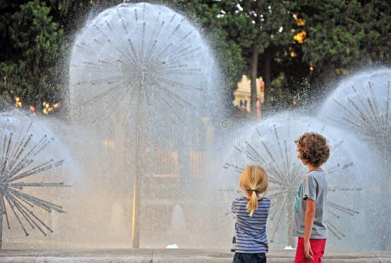 Zwei Kinder, die Brunnen betrachten stockfoto