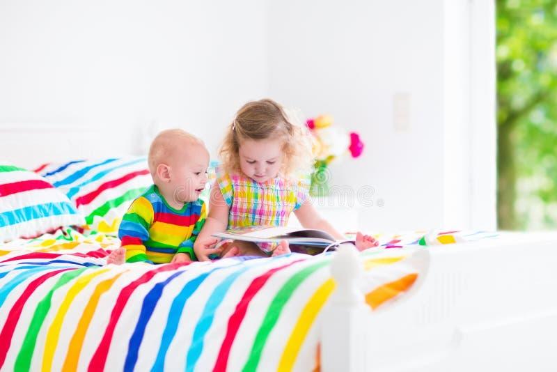 Zwei Kinder, die ein Buch im Bett lesen lizenzfreies stockfoto