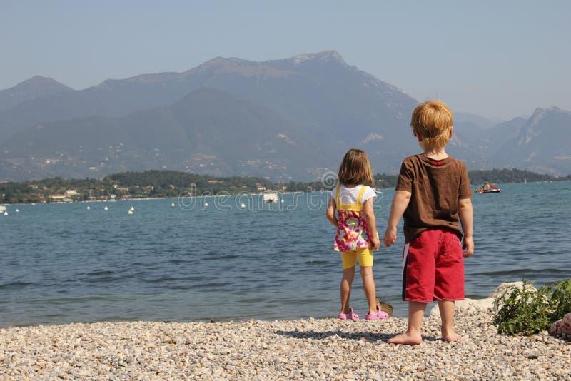 Zwei Kinder, die einen See betrachten stockbilder
