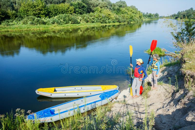 Zwei Kinder, die Kajakfahrt auf schönen Fluss genießen Wenig Jungen- und Jugendlichmädchen, das am heißen Sommertag Kayak fährt S lizenzfreie stockfotografie