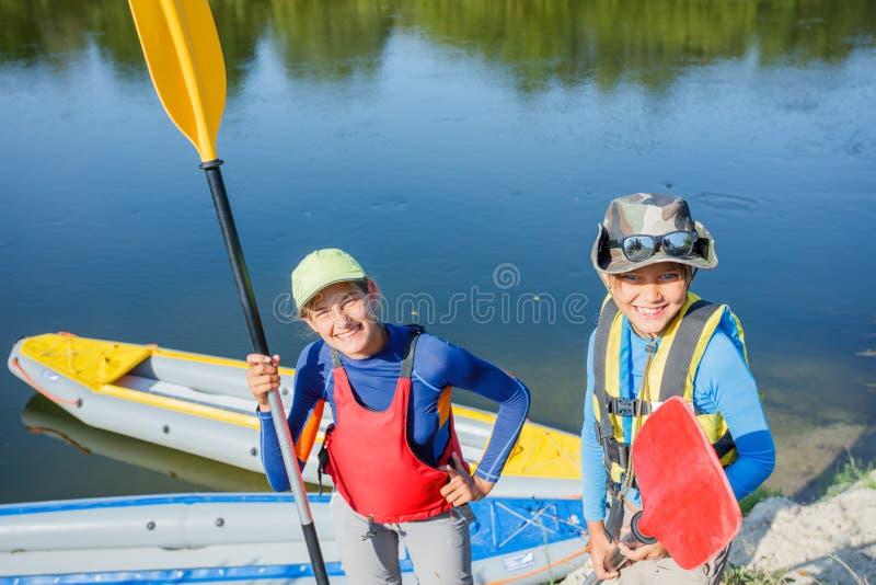 Zwei Kinder, die Kajakfahrt auf schönen Fluss genießen Wenig Jungen- und Jugendlichmädchen, das am heißen Sommertag Kayak fährt S lizenzfreie stockfotos
