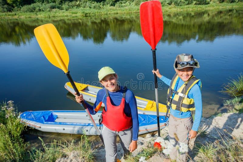 Zwei Kinder, die Kajakfahrt auf schönen Fluss genießen Wenig Jungen- und Jugendlichmädchen, das am heißen Sommertag Kayak fährt S stockbilder