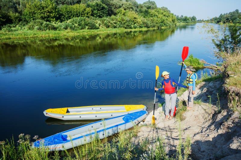 Zwei Kinder, die Kajakfahrt auf schönen Fluss genießen Wenig Jungen- und Jugendlichmädchen, das am heißen Sommertag Kayak fährt S stockfotos