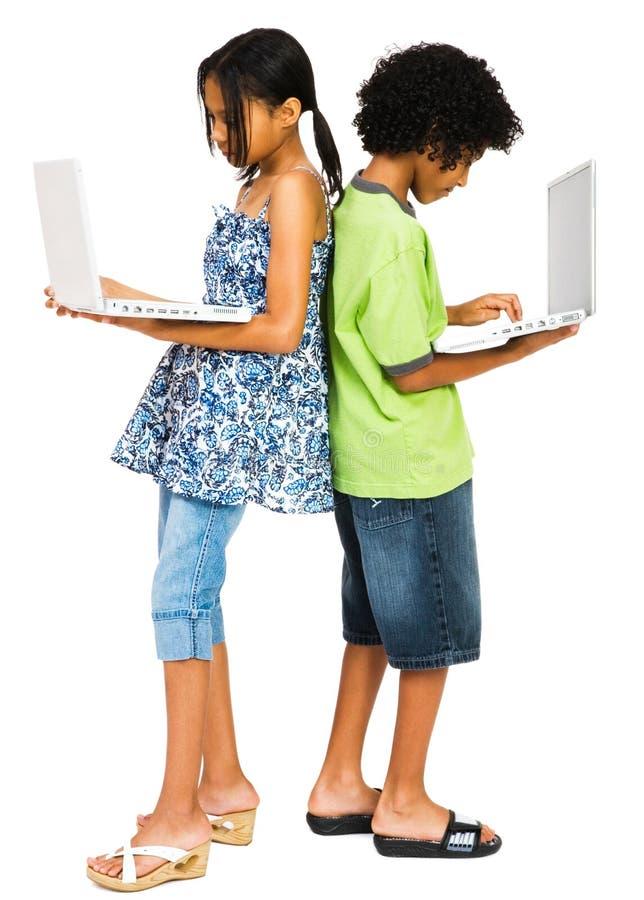 Zwei Kinder, die an Laptopen arbeiten stockfotos