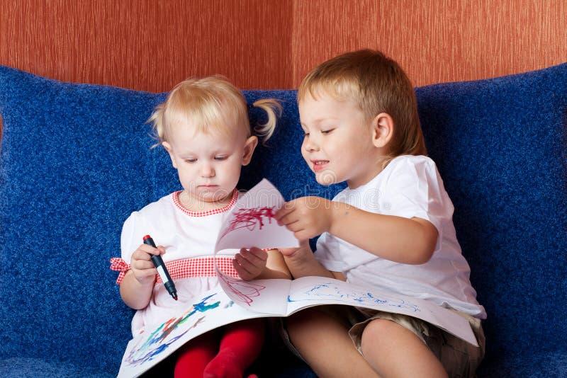 Zwei Kinder, die Malerei schauen lizenzfreie stockbilder