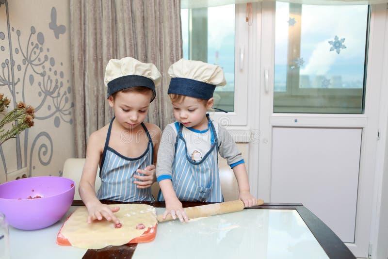 Zwei Kinder, die Mehlklöße kochen lizenzfreie stockfotografie