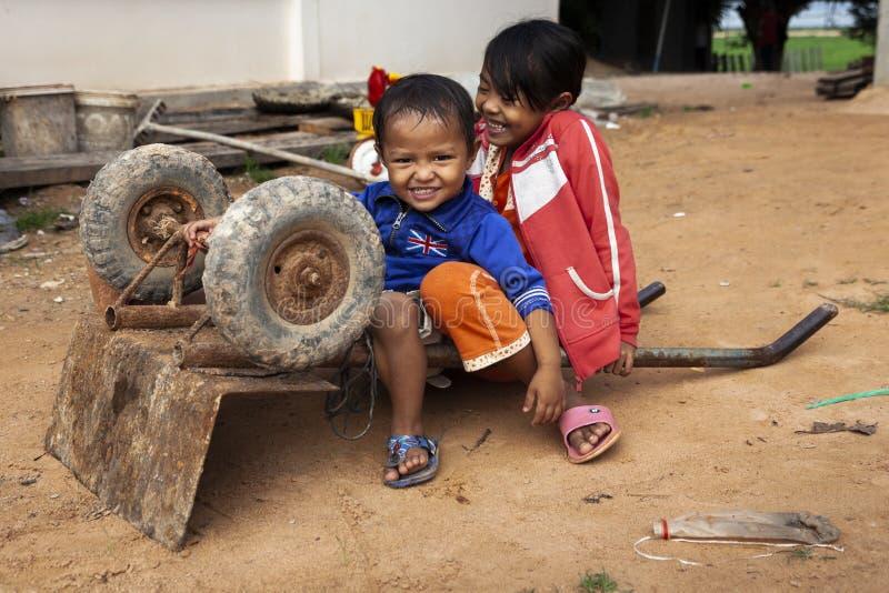 Zwei Kinder, die mit einer Schubkarre spielen lizenzfreies stockfoto