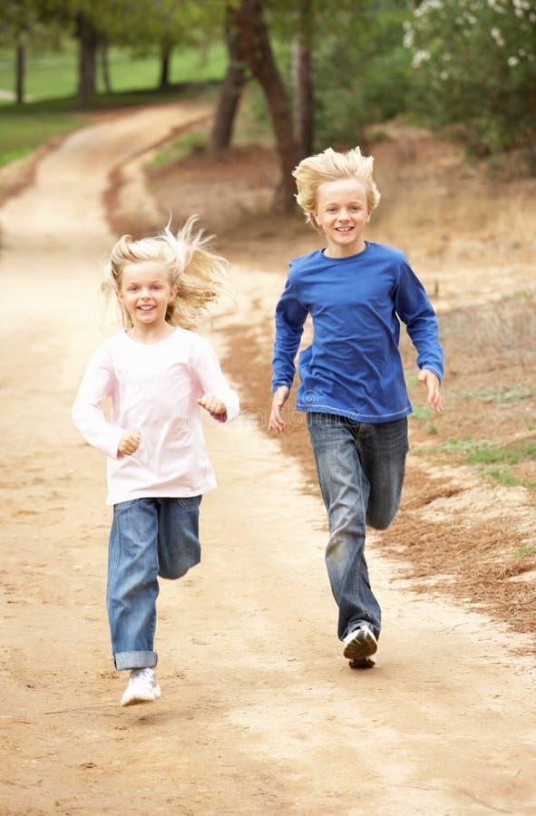 Zwei Kinder, die in Park laufen lizenzfreie stockfotografie