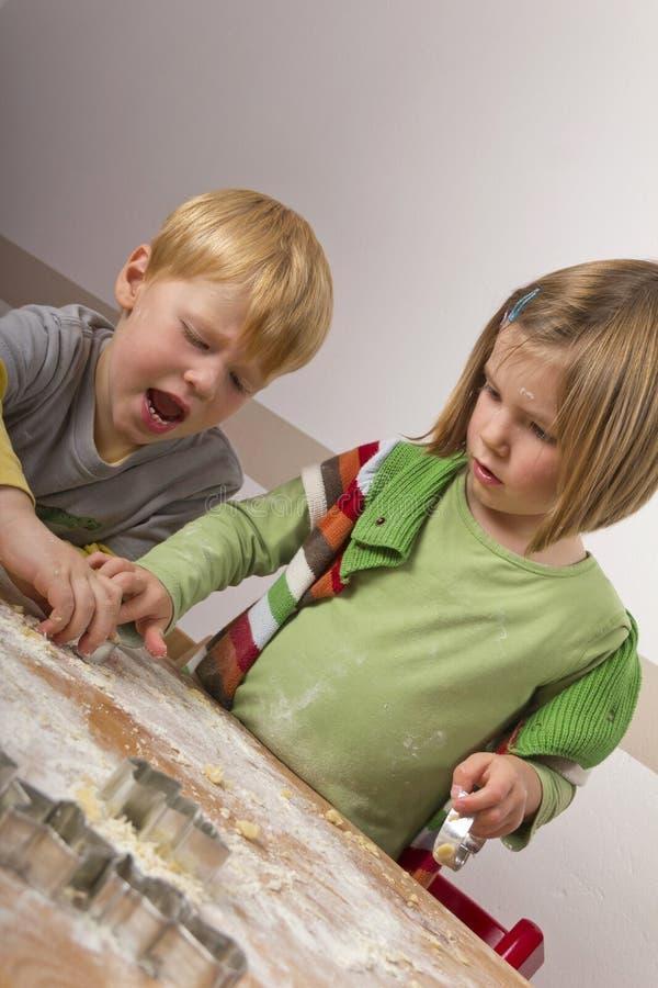 Zwei Kinder, die Plätzchen für Weihnachten schneiden stockfoto