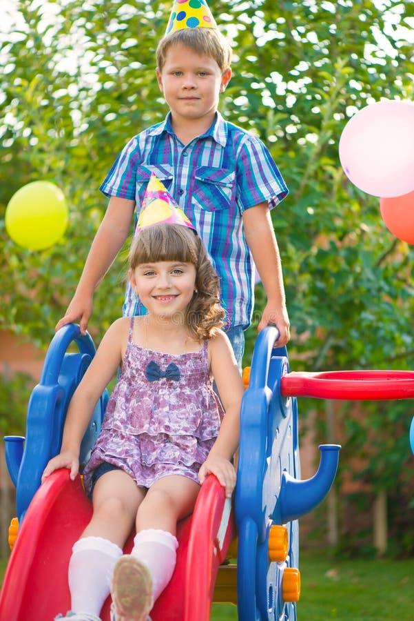 Zwei Kinder, die am Spielplatz schieben stockfotografie