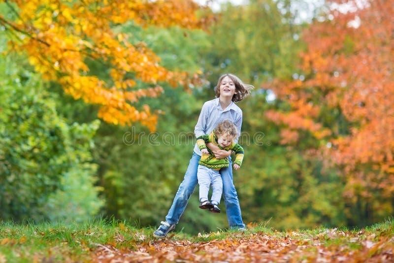Zwei Kinder, die togeter im Herbstpark spielen lizenzfreie stockfotos