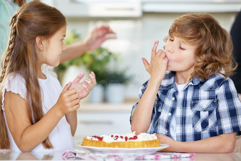 Zwei Kinder, die vom rote Johannisbeerfruchtkuchen schmecken stockfotos