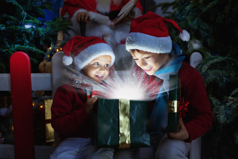 Zwei Kinder, die Weihnachtsgeschenk öffnen