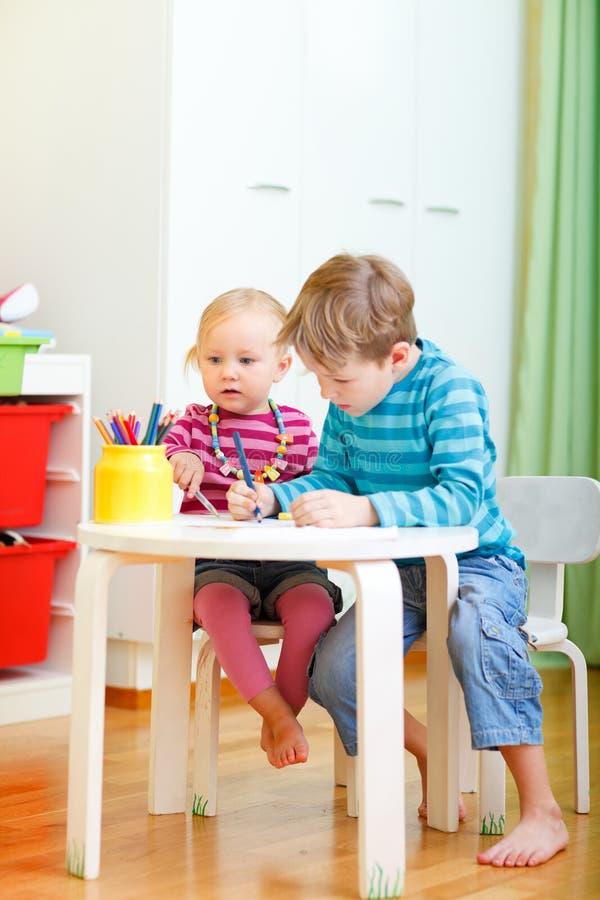 Zwei Kinder, die zusammen zeichnen lizenzfreie stockfotografie