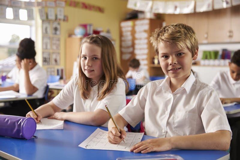 Zwei Kinder in einer Lektion an einer Grundschule schauen zur Kamera lizenzfreie stockfotos