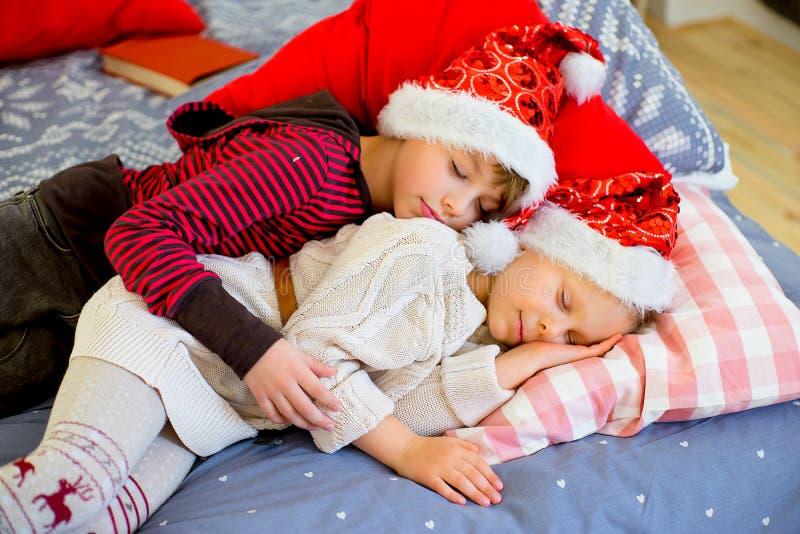 Zwei Kinder erhalten schläfrig, bis sie Weihnachten erwarten stockfoto
