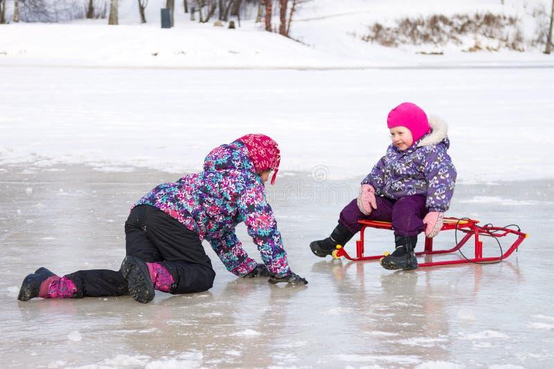 Zwei Kinder haben den Spaß, der zusammen auf dem Eis sitzt und mit einem Schneeschlitten an einem klaren Wintertag spielt lizenzfreies stockfoto