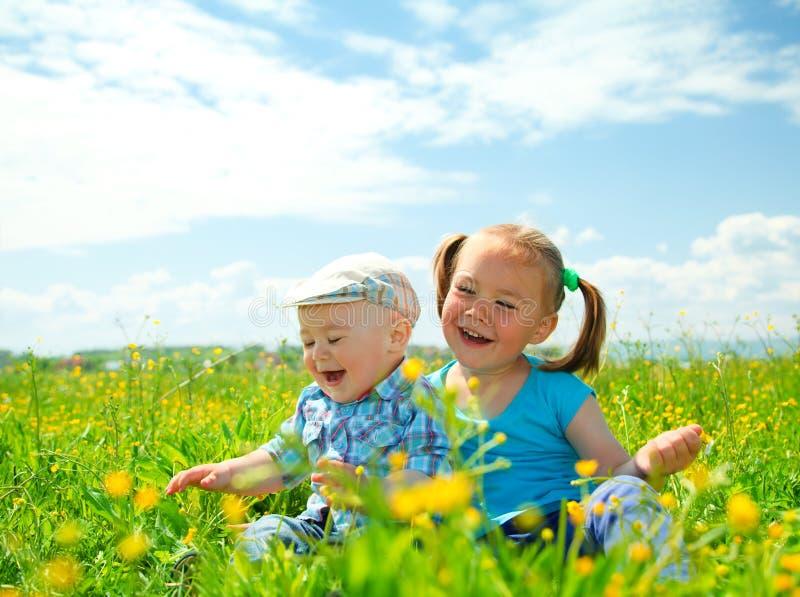 Zwei Kinder haben Spaß auf grüner Wiese lizenzfreie stockbilder