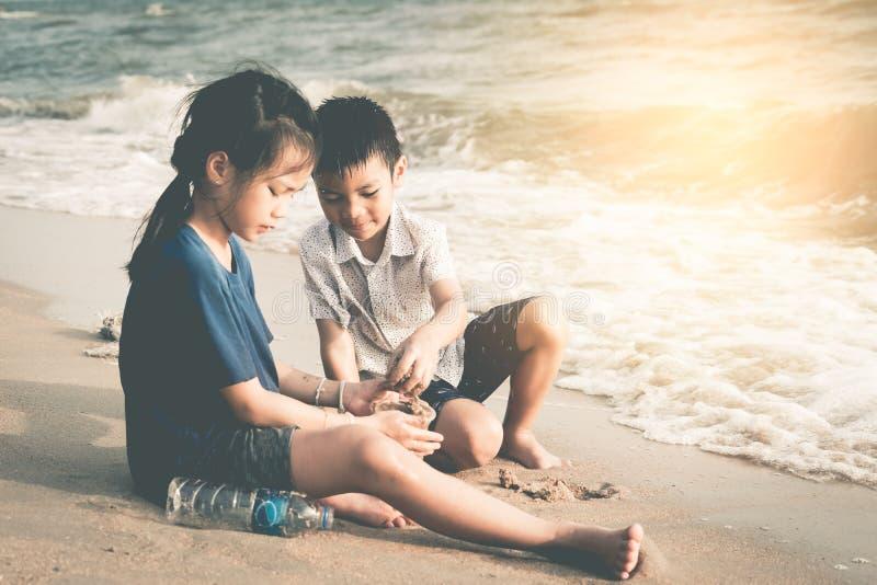Zwei Kinder hilft herauf das Säubern der Umwelt auf dem Strand lizenzfreie stockfotografie