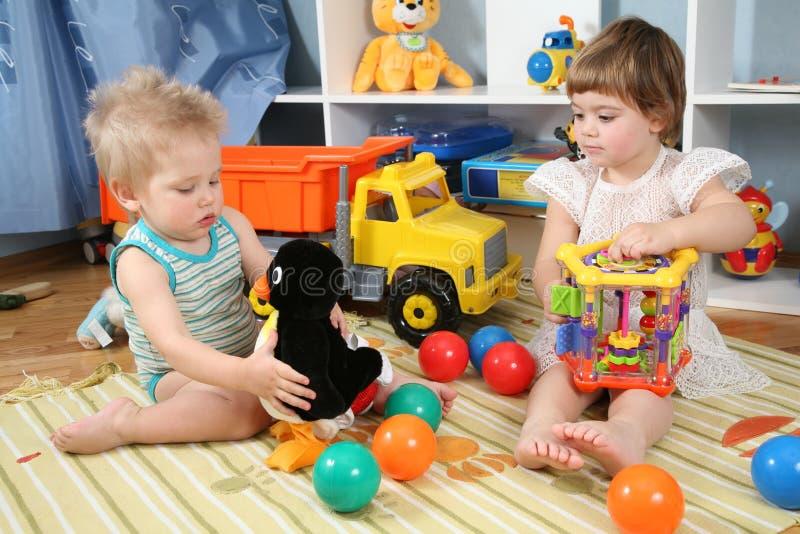 Zwei Kinder im Spielzimmer mit Spielwaren lizenzfreie stockfotografie