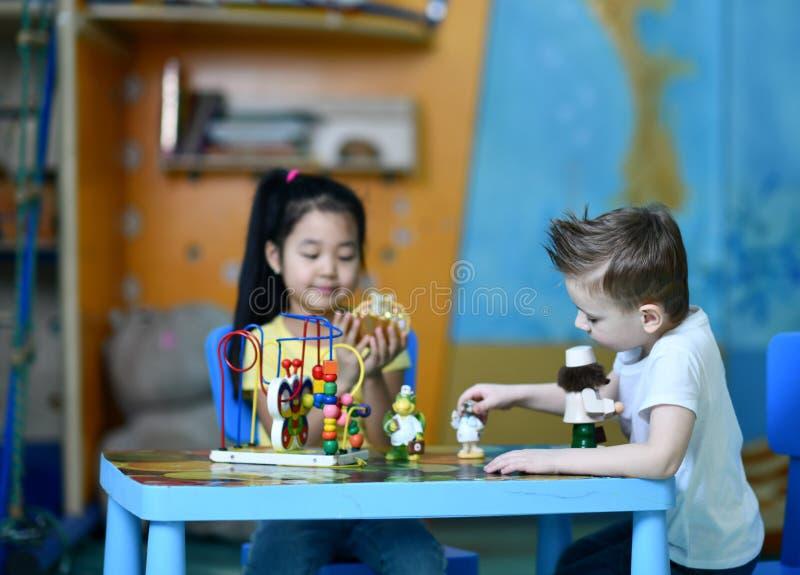 Zwei Kinder Junge und Mädchenspiel enthusiastisch an den Tabellenspielzeugdoktoren stockbilder