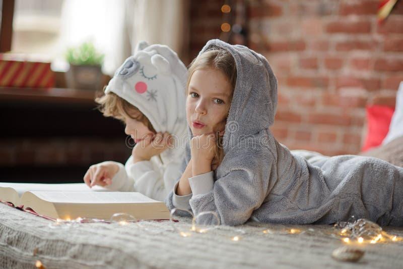 Zwei Kinder liegen auf dem großen Bett und lesen Weihnachtsgeschichten stockfotografie