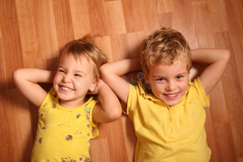 Zwei Kinder liegen auf Fußboden 3 lizenzfreie stockfotografie