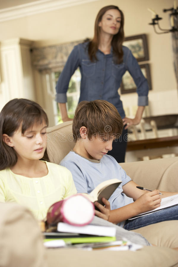 Zwei Kinder mit der Hausarbeit, die auf Sofa At Home Whilst Mother-Uhren sitzt stockfotos