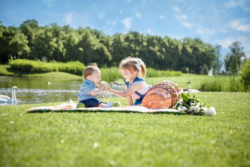 Zwei Kinder sitzen auf grüner Wiese und lächeln lizenzfreie stockbilder