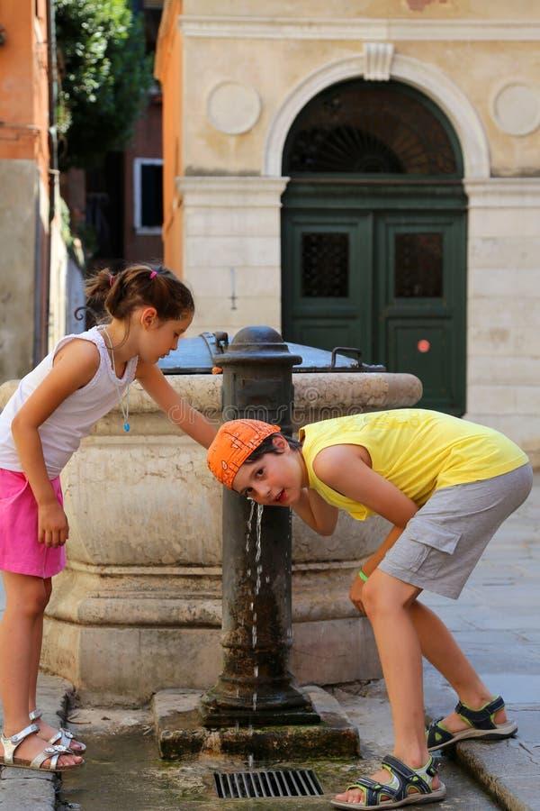 Zwei Kinder trinken Wasser von einem Brunnen auf der Insel von Venedig stockfoto