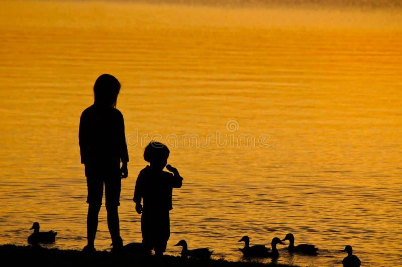 Zwei Kinder, welche die Ente speisen lizenzfreie stockfotos