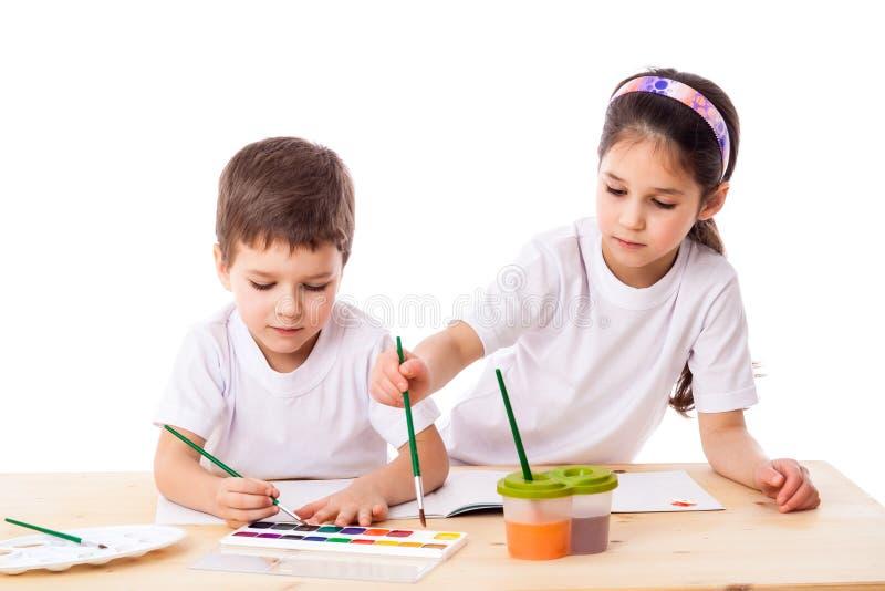 Zwei Kinder zeichnet mit Aquarell zusammen lizenzfreie stockfotografie