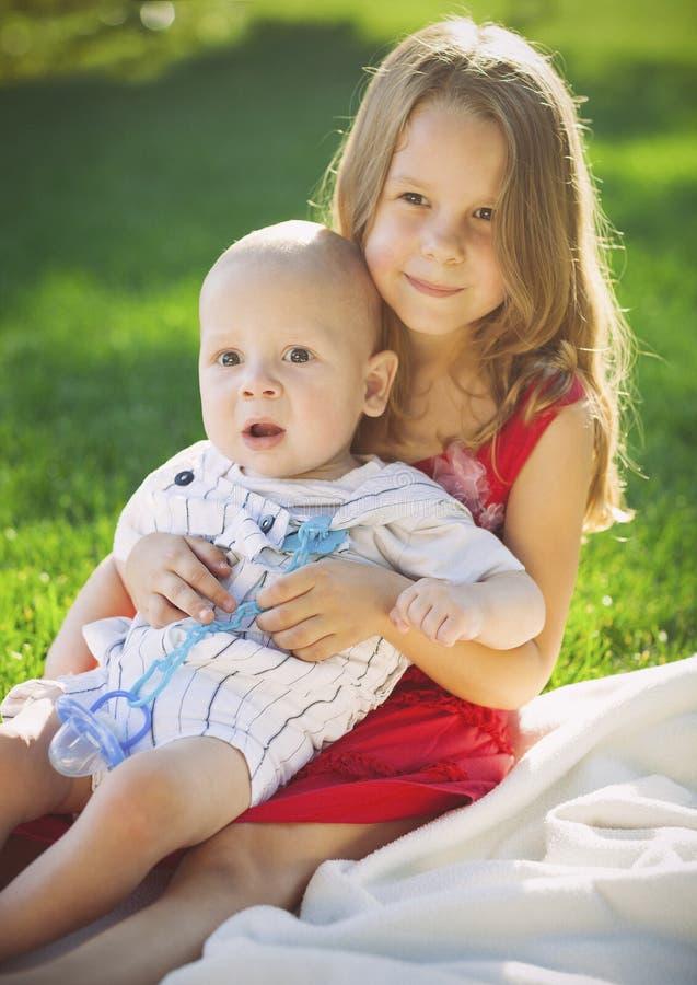 Zwei Kinderbabybruder und -schwester auf grüner Wiese lizenzfreie stockbilder