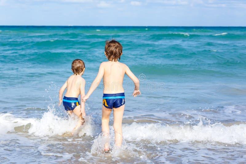 Zwei Kinderjungen, die auf Ozean laufen, setzen in Florida auf den Strand lizenzfreies stockbild