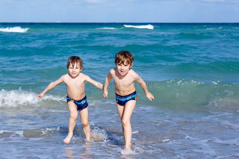Zwei Kinderjungen, die auf Ozeanstrand laufen Kleine Kinder, die Spaß haben stockbilder