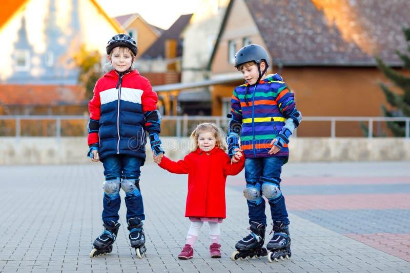 Zwei Kinderjungen und wenig Kleinkindmädchen, die zusammen draußen am sonnigen Tag spielen Brüder in der Schutzsicherheitskleidun stockbild