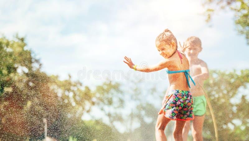 Zwei Kinderspiel mit dem Besprühen des Wassers im Sommergarten lizenzfreies stockfoto