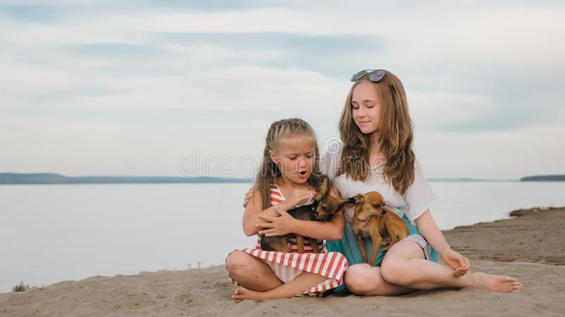Zwei Kinderspielen, das auf dem Sand auf dem Strand verfolgt stockbild
