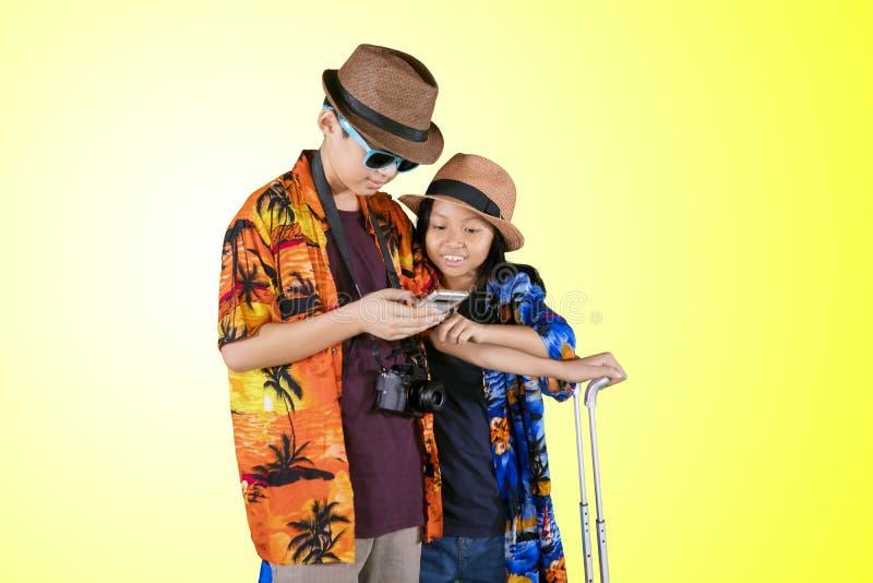 Zwei Kindertouristen, die ein Telefon auf Studio verwenden lizenzfreie stockfotografie