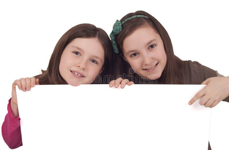 Zwei-klein-Mädchen-anhalten-ein-weiß-Fahne Lizenzfreies Stockbild