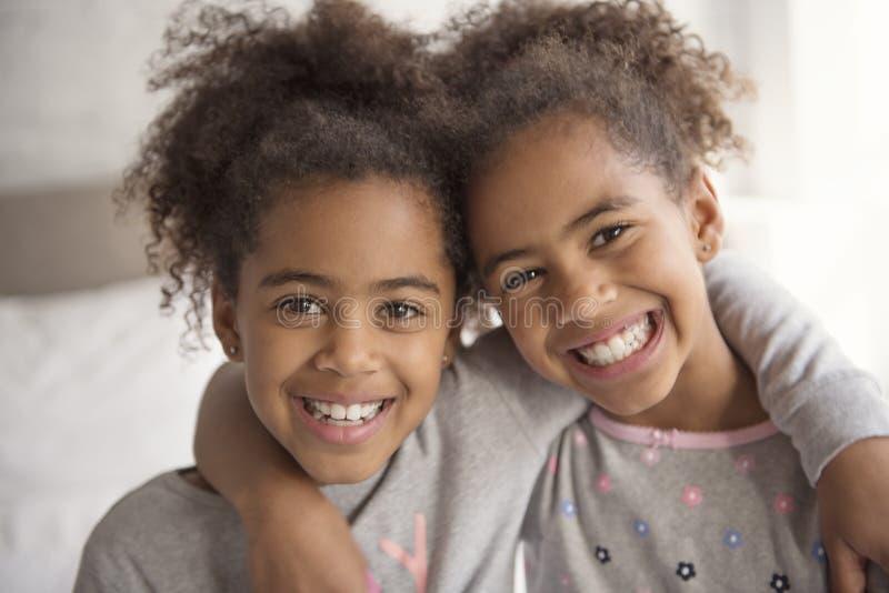 Zwei kleine Afroamerikanermädchen auf Bett zu Hause lizenzfreie stockfotos