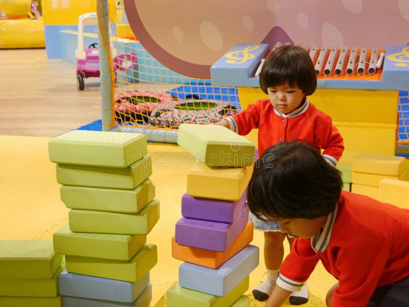 Zwei kleine asiatische Babys, die Schwestern, stapelnd herauf Schaummauerziegel/blockiert zusammen an einem Innenspielplatz lizenzfreie stockfotos