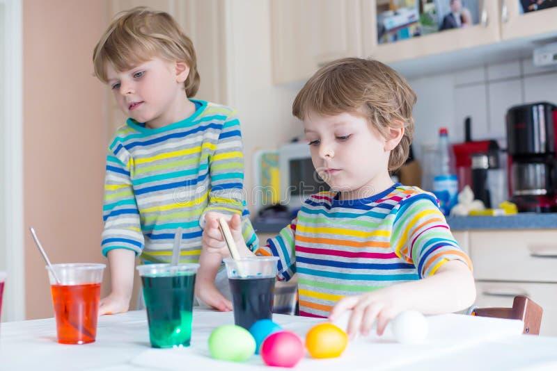 Zwei kleine blonde Kinderjungen, die Eier für Ostern-Feiertag färben stockbilder