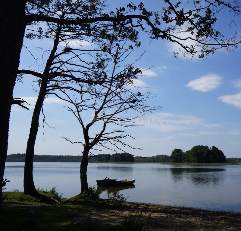 Zwei kleine Boote und dunkle Bäume durch den See an polnischem Masuria-Bezirk (Mazury) stockfoto