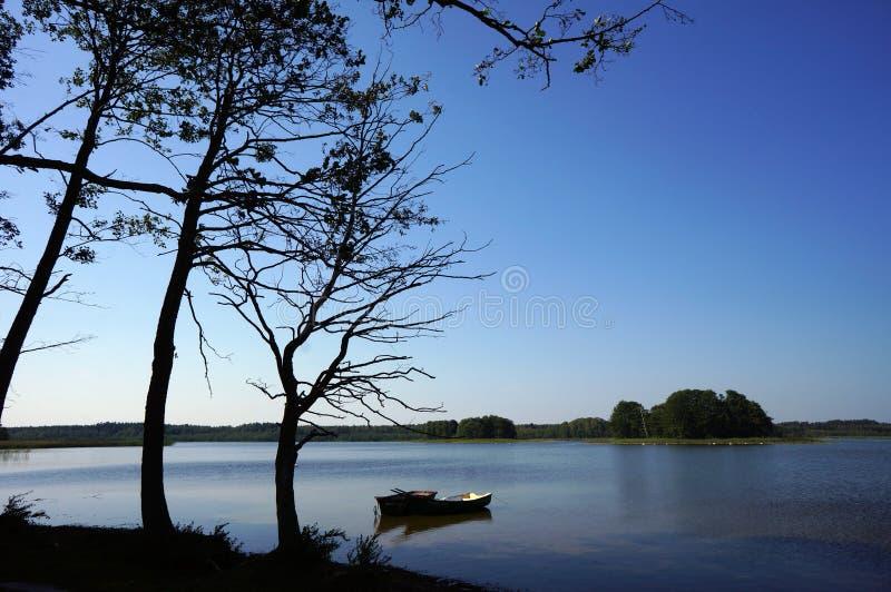 Zwei kleine Boote und ein toter Baum durch den See an polnischem Masuria-Bezirk (Mazury) lizenzfreie stockbilder