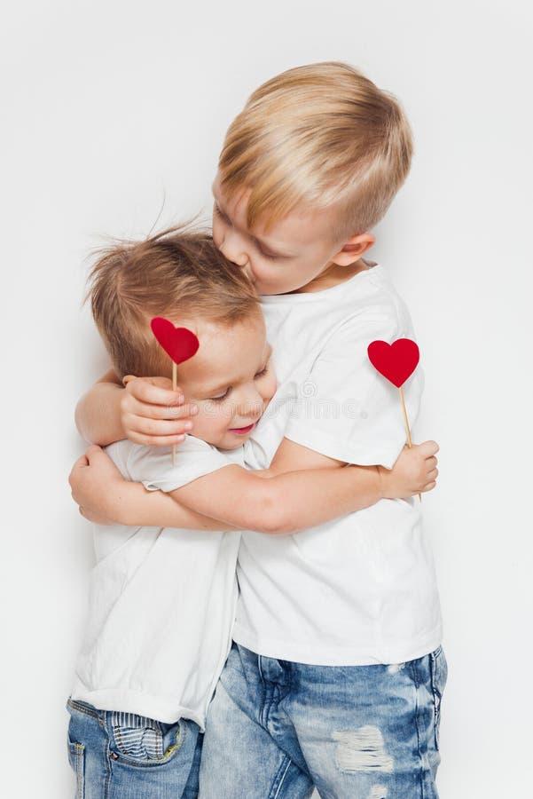 Zwei kleine Brüder, die ein Herzformzeichen umarmen und halten lizenzfreies stockfoto