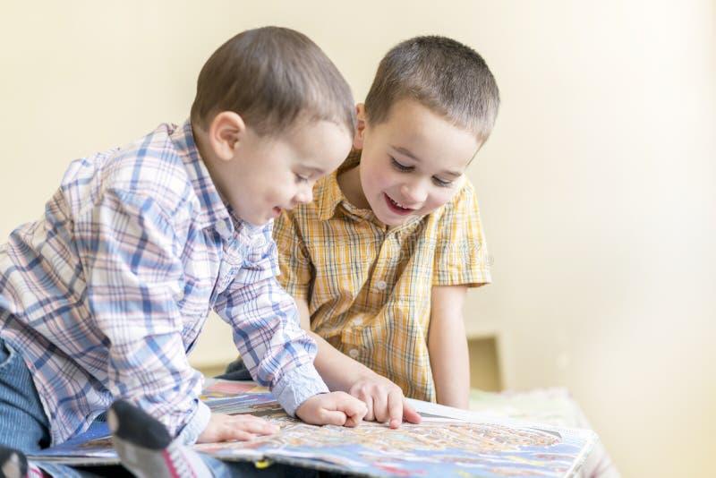 Zwei kleine Brüder lasen ein Kind-` s Buch Kind-` s Freundschaft, Spaßbildung lizenzfreies stockbild